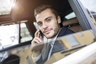 Young businessman in taxi chatting on smartphone - CUF24027