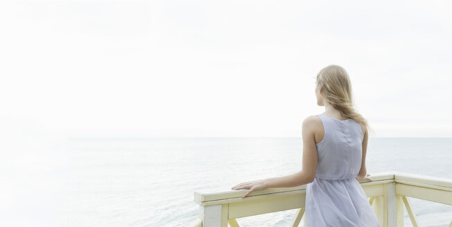 Rear view of young woman looking out to sea from balcony, Miami Beach, Florida, USA - CUF24060