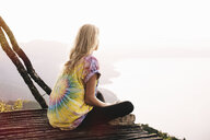 Young woman sitting on balcony looking out over Lake Atitlan, Guatemala - CUF24075