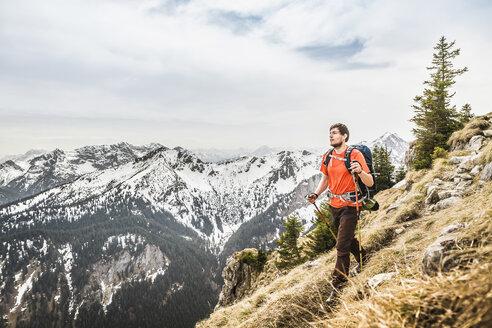 Young male hiker on peak of Klammspitze mountain, Oberammergau, Bavaria, Germany - CUF24099