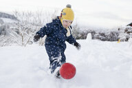 Boy kicking his ball in the snow - CUF24117