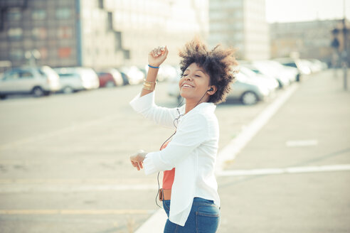 Young woman dancing to music on earphones in city - CUF24144