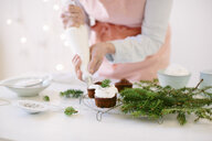 Woman icing chocolate cupcakes with whipped cream - CUF24192