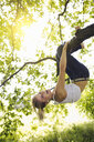 Young woman hanging upside down and holding onto tree branch - CUF24237