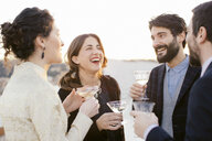 Group of friends laughing and drinking at party - CUF24318