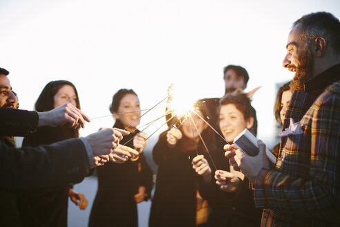 Group of friends touching sparklers at party - CUF24327