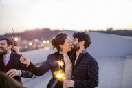 Heterosexual couple holding sparklers and kissing at party - CUF24333