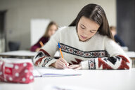 Teenage girl writing in exercise book in class - ZEF15657