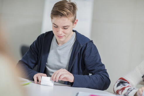 Teenage boy folding note in class - ZEF15669