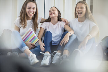 Happy teenage girls sitting on floor in school - ZEF15723