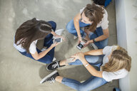 Teenage girls sitting on the floor with cell phones and talking - ZEF15729