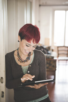 Young woman at home using digital tablet - CUF24498