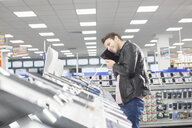 Young male shopper holding up chosen digital tablet in electronics store - CUF24615