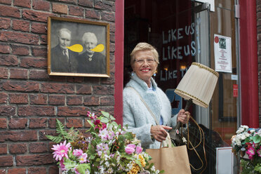 Mature female customer carrying lamp and shopping bag outside vintage shop - CUF24639