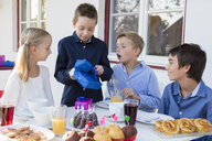 Boy with siblings unwrapping birthday gifts on patio - CUF24687