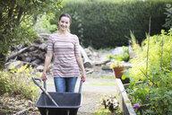 Portrait of female gardener pushing wheelbarrow in rustic organic garden - CUF24702