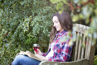 Mid adult woman reading on garden bench at Thornbury Castle, South Gloucestershire, UK - CUF24705