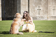 Woman posing with cup of tea and golden retriever dog at Thornbury Castle, South Gloucestershire, UK - CUF24708