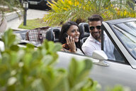 Mid adult couple in convertible car, woman using smartphone - CUF24753