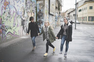Three sisters walking by graffiti wall - CUF24834