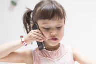 Portrait of little girl on the phone looking down - DRF01738