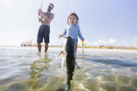 Daughter watching father catch fish in sea, Fort Walton Beach, Florida, USA - ISF09367