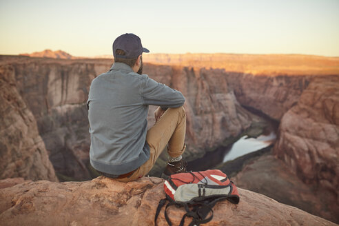 Man sitting on rock, looking at view, rear view, Page, Arizona, USA - ISF09379