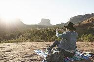 Woman sitting on blanket in desert, photographing view, using smartphone, Sedona, Arizona, USA - ISF09391