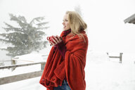 Young woman in snowy mist wrapped in red blanket drinking coffee - CUF25024