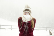 Young woman blowing handful of powder snow - CUF25027