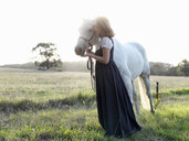 Portrait of teenage girl with grey horse in sunlit field - CUF25033