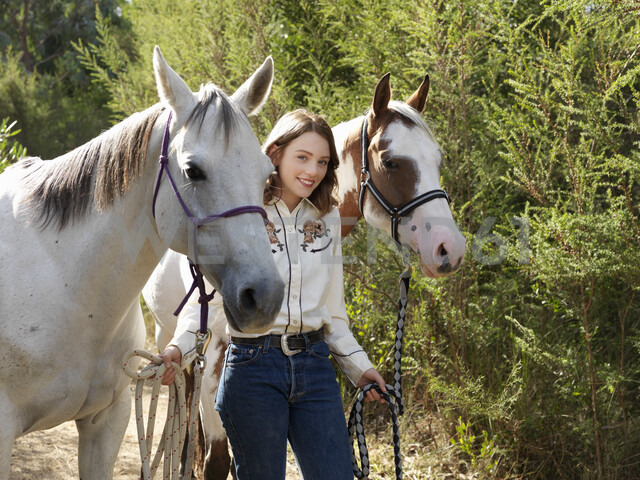 Portrait of teenage girl leading two horses - CUF25036 - Elke Meitzel/Westend61