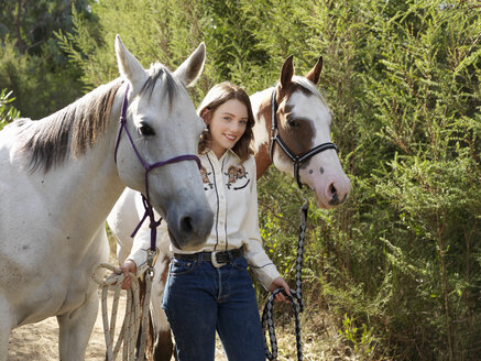 Portrait of teenage girl leading two horses - CUF25036