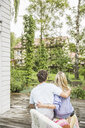 Rear view of couple sitting on garden patio - CUF25165