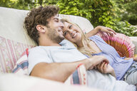 Romantic couple sitting on vintage sofa in garden - CUF25177