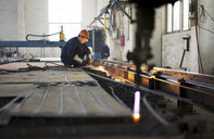Worker using equipment in crane manufacturing facility, China - CUF25231