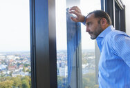 Businessman leaning against office window gazing at Brussels cityscape, Belgium - CUF25243