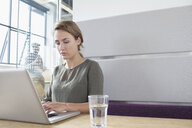 Young woman typing on laptop in office - CUF25321