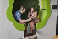 Male and female designers working on digital tablet in tree shaped office space - CUF25333