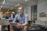 Portrait of young man using digital tablet in office - CUF25345
