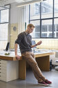 Male designers looking smartphone in creative office - CUF25351