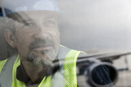 Portrait of airport worker looking out of window at airplane - CUF25468