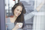 Portrait of young woman at apartment window drinking coffee - CUF25531
