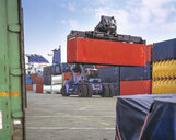 Stacker lifting shipping container in port, Grimsby, England, United Kingdom - CUF25603