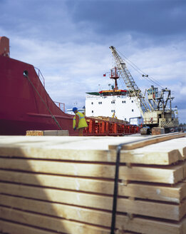 Worker unloading timber from cargo ship in port, Grimsby, England, United Kingdom - CUF25606