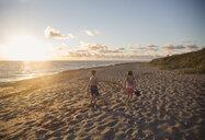 Boy and sister walking along beach at sunrise, Blowing Rocks Preserve, Jupiter Island, Florida, USA - ISF09427