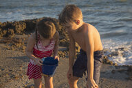Girl and brother peering into toy bucket on beach, Blowing Rocks Preserve, Jupiter Island, Florida, USA - ISF09433