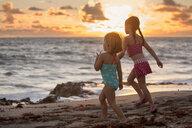 Girl and sister running on beach at sunrise, Blowing Rocks Preserve, Jupiter Island, Florida, USA - ISF09436