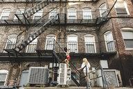 Women climbing fire escape ladder of apartment building, Boston, MA, USA - ISF09523