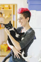 Young woman with pink carrying wide-eyed cat in kitchen - ISF09541